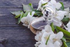 Bottiglia dei fiori del gelsomino su fondo di legno Profumo profumato del gelsomino fotografia stock libera da diritti