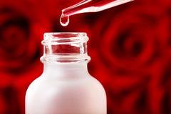 Bottiglia del contagoccia con le rose rosse Fotografia Stock Libera da Diritti