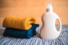 Bottiglia del detersivo e un mucchio dei maglioni immagine stock