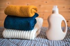 Bottiglia del detersivo e un mucchio dei maglioni fotografie stock libere da diritti