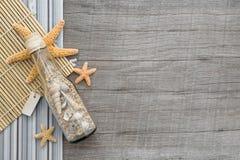 Bottiglia del ricordo con la sabbia e conchiglie su fondo di legno immagini stock