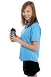 Bottiglia del sipper della holding della ragazza. Rottura dall'allenamento di ginnastica Immagini Stock Libere da Diritti