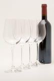 Bottiglia del vino rosso con i bicchieri di vino allineati Fotografia Stock