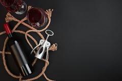 Bottiglia del vino rosso, due vetri e cavaturaccioli su fondo nero Vista superiore con lo spazio della copia Fotografia Stock
