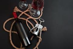 Bottiglia del vino rosso, due vetri e cavaturaccioli su fondo nero Vista superiore con lo spazio della copia Fotografie Stock