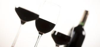 Bottiglia del vino rosso e tre vetri su fondo bianco Immagini Stock
