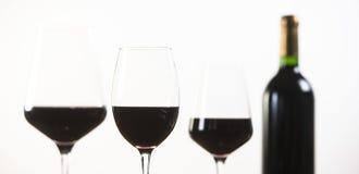 Bottiglia del vino rosso e tre vetri su fondo bianco Fotografia Stock Libera da Diritti