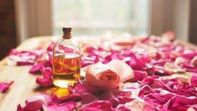 Bottiglia dell'olio dell'aroma con i petali di rose su superficie di legno, fuoco selezionato immagini stock libere da diritti