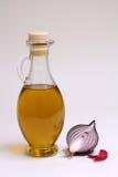 Bottiglia dell'olio di oliva con la cipolla rossa Fotografia Stock