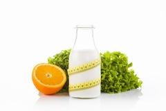 Bottiglia della bevanda della proteina avvolta con nastro adesivo di misurazione giallo con lattuga verde nei precedenti bianchi Immagine Stock