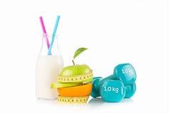 Bottiglia della bevanda della proteina e della metà della mela e dell'arancia avvolte con una misura di nastro gialla Fotografia Stock Libera da Diritti