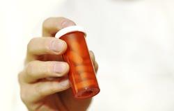Bottiglia della holding del medico delle pillole di prescrizione immagini stock
