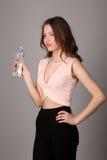 Bottiglia della holding della ragazza di acqua Fine in su Fondo grigio Immagini Stock