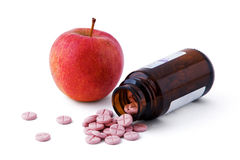 Bottiglia della medicina della pillola di vetro marrone e della mela rossa isolate su fondo bianco Immagini Stock Libere da Diritti