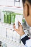 Bottiglia della medicina di Reading Instructions On della donna di affari a Pharmac Fotografia Stock Libera da Diritti