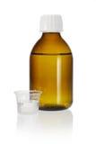 Bottiglia della medicina e tazza di misurazione Immagini Stock Libere da Diritti