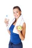 Bottiglia della tenuta della donna di forma fisica di acqua e della mela isolate su briciolo Immagini Stock