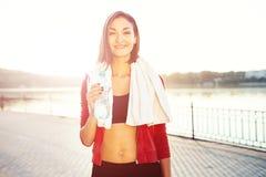Bottiglia della tenuta della donna di acqua e di un asciugamano Fotografie Stock