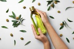 Bottiglia della tenuta della donna di olio d'oliva su fondo leggero fotografie stock libere da diritti