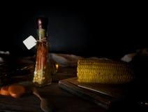 Bottiglia delle carote e del cereale inscatolati, spezie su una tavola di legno Fondo scuro Immagine Stock Libera da Diritti