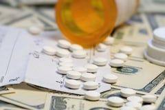 Bottiglia delle pillole di prescrizione sopra le banconote in dollari Fotografia Stock Libera da Diritti