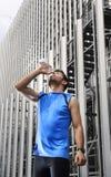 Bottiglia di acqua bevente del giovane uomo di sport dopo il corso di formazione corrente nel distretto aziendale Fotografia Stock
