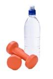 Bottiglia di acqua con i pesi di forma fisica Fotografie Stock Libere da Diritti