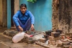Bottiglia di acqua di riempimento del giovane uomo indiano Fotografia Stock