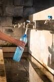 Bottiglia di acqua di riempimento della mano Immagine Stock Libera da Diritti