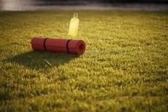 Bottiglia di acqua e della stuoia rotolata su erba verde Fotografia Stock Libera da Diritti