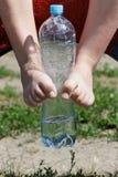 Bottiglia di acqua e gambe Immagini Stock Libere da Diritti