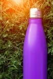 Bottiglia di acqua inossidabile del termos, colore porpora viola Modello isolato sul fondo dell'erba verde con effetto di luce so fotografia stock