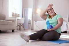 Bottiglia di acqua di peso eccessivo della tenuta della giovane donna Immagini Stock
