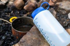 Bottiglia di acqua su roccia dal vaso fotografia stock libera da diritti