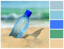 Bottiglia di acqua sulla spiaggia con i campioni di colore della tavolozza Fotografia Stock