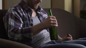 Bottiglia di birra alcolica di apertura con la forcella sul sofà domestico, dipendenza non sana di abitudine stock footage