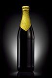 Bottiglia di birra con stagnola dorata isolata su fondo nero Fotografia Stock