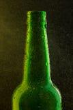 Bottiglia di birra fredda con le gocce sul nero Fotografie Stock