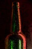 Bottiglia di birra fredda con le gocce sul nero Fotografia Stock