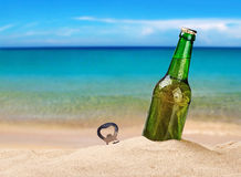 Bottiglia di birra su una spiaggia sabbiosa Fotografia Stock