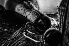 Bottiglia di birra vuota in bianco e nero sulla tavola di legno Fotografia Stock