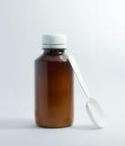 Bottiglia di Brown dello sciroppo di tosse con il cucchiaio di plastica bianco Fotografie Stock