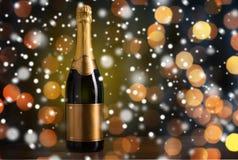 Bottiglia di champagne con l'etichetta dorata sopra neve Fotografia Stock