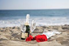 Bottiglia di Champagne, vetri, rose alla spiaggia Fotografie Stock Libere da Diritti