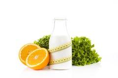 Bottiglia di latte avvolta con una misura di nastro gialla di plastica con due metà dell'arancia con lattuga verde Immagini Stock Libere da Diritti
