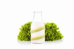 Bottiglia di latte avvolta con una misura di nastro gialla di plastica con lattuga verde nei precedenti bianchi Fotografia Stock Libera da Diritti