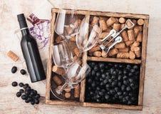 Bottiglia di lusso di vino rosso e di vetri vuoti con l'uva scura con i sugheri ed apri dentro la scatola di legno d'annata su fo fotografie stock