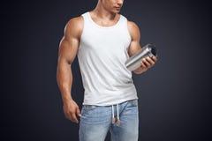Bottiglia di modello maschio di scossa della proteina della tenuta di forma fisica muscolare Fotografie Stock Libere da Diritti