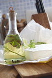 Bottiglia di olio con le erbe ed il formaggio Fotografia Stock