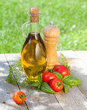 Bottiglia di olio d'oliva, agitatore del pepe, pomodori ed erbe Fotografia Stock